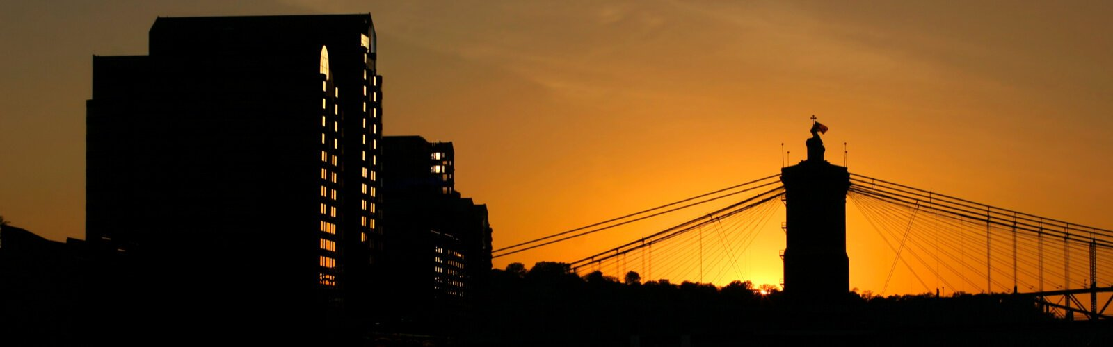 The sun sets behind the John A. Roebling Suspension Bridge and the NKY riverfront.