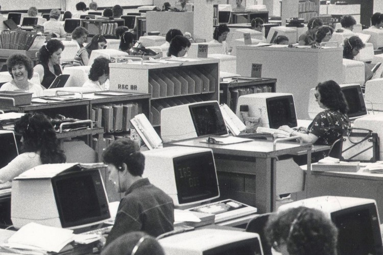 A vintage photo from the center's interior of workers processing tax returns.