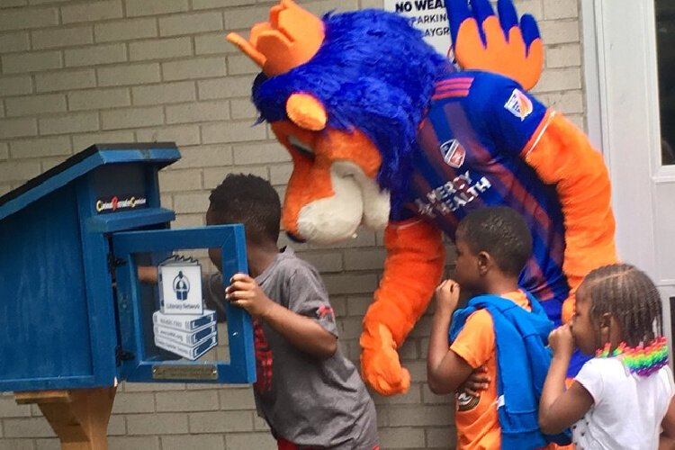 Children wait their turn to look through the Little Free Library at the Cincinnati Recreation Center in Millvale, installed by the Literacy Network of Greater Cincinnati.