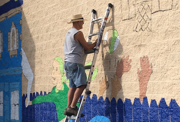 "Local artist Kevin T. Kelly works on the ""Love the Cov"" mural"