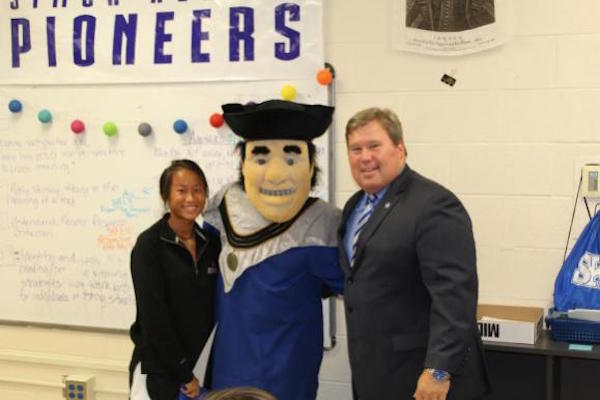 "Kendal Burns of Simon Kenton poses with Thomas More President David A. Armstrong and Saints Mascot ""Tommy Mo"""