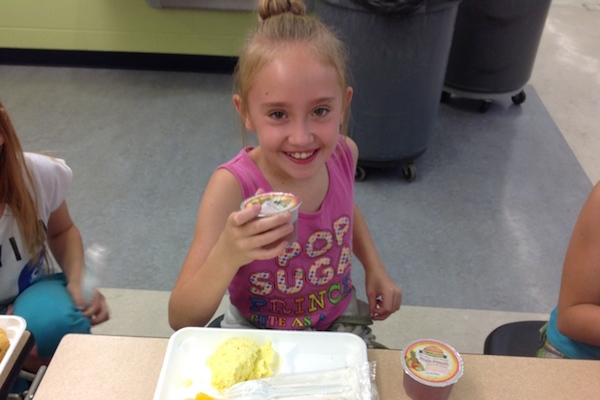 Annabell Roberts shows off her breakfast at UpSpring's Summer 360 camp location at Caywood Elementary in Edgewood